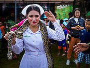 "13 JANUARY 2018 - BANGKOK, THAILAND:      A Thai army nurse salutes while holding a python during Children's Day activities at the Royal Thai Army's King's Guard 2nd Cavalry Camp in central Bangkok. Children's Day is called ""Wan Dek"" in Thai. Many government offices and military bases hold special activities for children as do shopping malls.  PHOTO BY JACK KURTZ"
