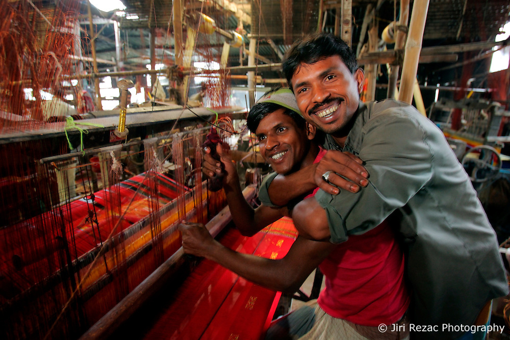 BANGLADESH SIRAJGANJ SAJANTULI 1FEB07 - Weavers enjoy a light moment as they toil at their handlooms in a rural sweatshop containing 60 looms in rural Sirajganj. Records of an indigenous weaving industry based on handlooms producing cotton fabrics date back to the 13th century in this area...jre/Photo by Jiri Rezac..© Jiri Rezac 2007..Contact: +44 (0) 7050 110 417.Mobile:  +44 (0) 7801 337 683.Office:  +44 (0) 20 8968 9635..Email:   jiri@jirirezac.com.Web:    www.jirirezac.com..© All images Jiri Rezac 2007 - All rights reserved.