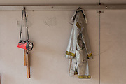 A protective jacket and torch hang in the remains of a fire station in the town of Tomioka, Futaba District of Fukushima, Japan. Monday April 29th 2013. The town was evacuated on March 12th after the March 11th 2011 earthquake and tsunami cause meltdowns at the nearby Fukushima Daichi nuclear power station. It lies well within the 20 kms exclusion zone though parts of the town were opened in spring 2013 again to allow locals to visit their property during daylight hours.