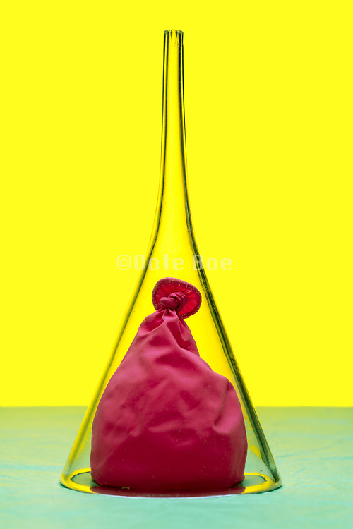 half depleted balloon under a glass siphon