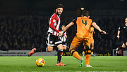 Marco Djuricin plays a forward ball past Alex Bruce during the Sky Bet Championship match between Brentford and Hull City at Griffin Park, London, England on 3 November 2015. Photo by Michael Hulf.