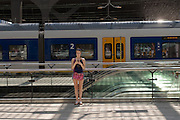 Op station Rotterdam Centraal wacht een meisje op de trein terwijl ze bezig is met haar telefoon. Wegens verwachte warmte zet NS op sommige trajecten minder treinen in.<br /> <br /> At Rotterdam Central Station a girl is busy with her phone while waiting for the train.