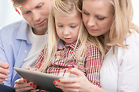 Mid adult parents using tablet PC with daughter at home