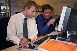 Man with cerebral palsy working as technical assistant in visual communications office; sitting at desk looking at computer with office manager,