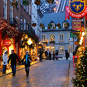 The quaint old shopping street of Rue St-Pierre in Quebec City's Old Town, decorated for Christmas and taken at night. In the background is the funicular going up the cliff face.