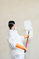 Female worker in protective workwear painting wall