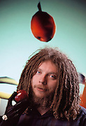 Virtual reality: Jaron Lanier, head of VPL Research of Redwood City, California, photographed surrounded by demonstration images of the virtual, non-real worlds that VPL have created. Fiber- optic sensors in the black rubber glove Lanier is wearing transmit a user's movements into the computer-generated virtual environment. A user's view of such a world is projected by the computer into 2 eye phones mounted on a headset. Model Released (1990)