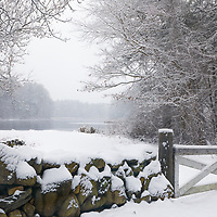 Snow covered stone wall and gate with the Wayside Inn Grist Mill pond in Sudbury Massachusetts during a New England winter snowstorm.<br />