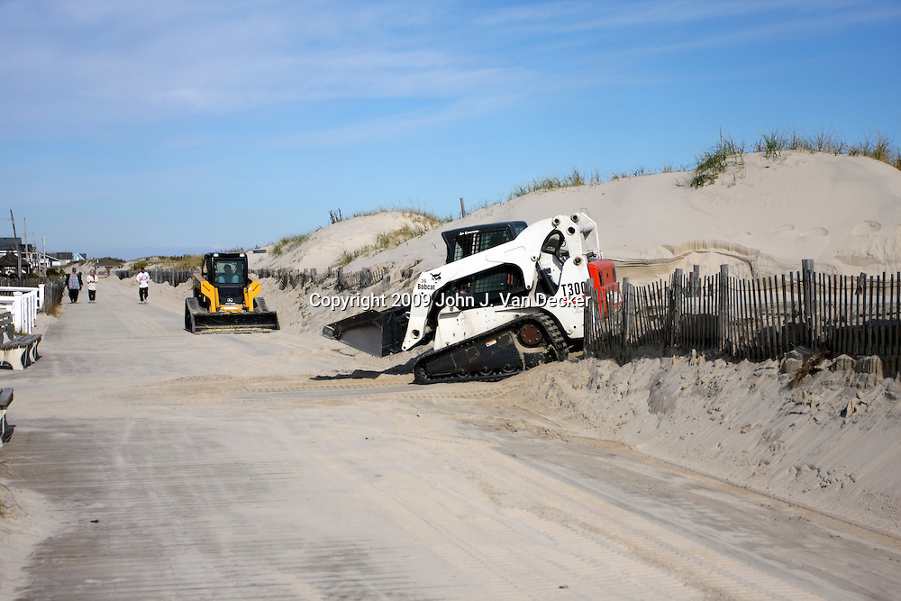 Front-end loaders clearing sand from boardwalk, Lavalette, New Jersey, USA. The front-end loaders move sand blown by storm winds from the beach back through the protective dunes to the beach.