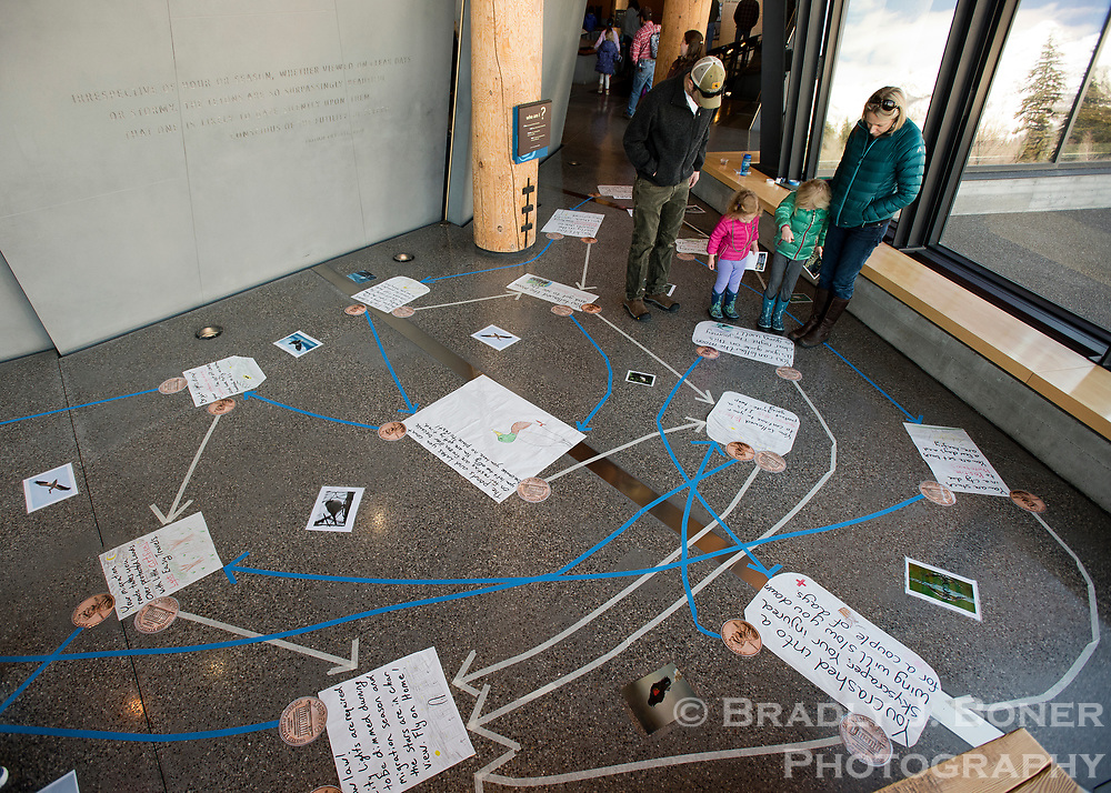 Erik and Jennifer Balsa, of Jackson, navigate the migratory paths of birds during Junior Ranger Day at the Craig Thomas Discovery and Visitor Center in Grand Teton National Park. The display showed kids the risks birds endure on their annual migratory journeys.