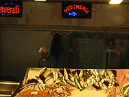 Fish vendor stands over he selection in the central market of Siracusa, Italy in 2012.