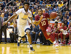 Jan 18, 2017; Morgantown, WV, USA; Oklahoma Sooners guard Jordan Woodard (10) drives baseline past West Virginia Mountaineers forward Brandon Watkins (20) during the second half at WVU Coliseum. Mandatory Credit: Ben Queen-USA TODAY Sports