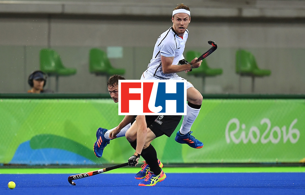 New Zealand's Hugo Inglis (bottom) vies with Germany's Christopher Ruhr during the men's quarterfinal field hockey Germany vs New Zealand match of the Rio 2016 Olympics Games at the Olympic Hockey Centre in Rio de Janeiro on August 14, 2016. / AFP / MANAN VATSYAYANA        (Photo credit should read MANAN VATSYAYANA/AFP/Getty Images)