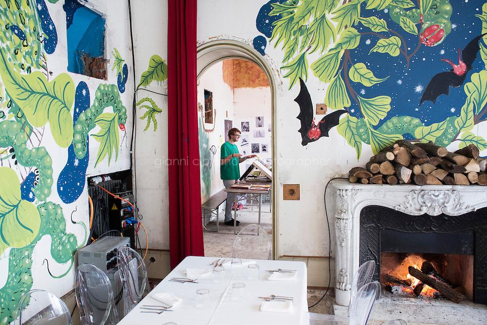 GENTILINO, SWITZERLAND - 26 October 2013: L'AM, L'Arte della Memoria at Villa Ambrosetti in Gentilino, Switzerland, on October 26th 2013.<br /> <br /> Il 26 e 27 ottobre un&rsquo;abitazione privata in disuso, destinata alla demolizione, viene investita dalle arti e aperta al pubblico prima della sua distruzione.<br /> <br /> 23 artisti contemporanei locali e internazionali sono stati invitati ad intervenire al suo interno ispirandosi al tema della memoria. Attraverso forme d&rsquo;arte come la pittura su muro, l&rsquo;installazione o la performance, gli spazi della Villa vengono cos&igrave; reinterpretati. Se alcuni artisti hanno gi&agrave; iniziato a lavorare, altri realizzeranno le proprie opere in loco tra 26 e il 27 ottobre 2013, permettendo cos&igrave; al pubblico di assistere in diretta alla loro creazione.<br /> <br /> Si tratta dunque di una mostra temporanea, effimera e strettamente legata ad un luogo e alla sua memoria. Di essa rester&agrave; solo un ricordo, delle immagini, un catalogo; tutte le opere create in situ verranno infatti distrutte insieme alla Villa nel gennaio del 2014, ricordandoci cos&igrave; che tutto ci&ograve; che &egrave; terreno &egrave; destinato ad accogliere i cambiamenti dati dall&rsquo;inevitabile scorrere del tempo.<br /> <br /> Oltre alle arti visive, anche la musica dal vivo sar&agrave; la protagonista di questi due giorni di festa: eseguita da band internazionali e da importanti volti provenienti dal panorama jazzistico ticinese, sapr&agrave; fare da filo conduttore interagendo con le opere artistiche presenti. La realizzazione e la successiva distruzione di un mandala di sabbia da parte di due monaci buddhisti, andr&agrave; a rafforzare ancor di pi&ugrave; il significato di queste due giornate, dedicate alla caducit&agrave; della vita.<br /> <br /> l&rsquo;AM - l&rsquo;arte della memoria &egrave; anche molto di pi&ugrave;: durante questi due giorni il pubblico potr&agrave; familiarizzare con la realt&agrave; dell&rsquo;editor