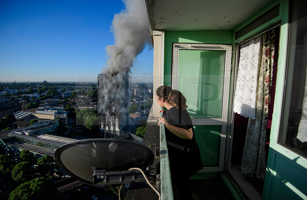 © Licensed to London News Pictures. 14/06/2017. London, UK. A woman looks out from her balcony at the scene of a huge fire at Grenfell tower block in White City, London. The blaze engulfed the 27-storey building with 200 firefighters attending the scene. There were reports of people trapped in the building. Photo credit: Ben Cawthra/LNP