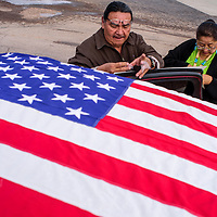 Ken Brown, left, and Carolene Whitman-Yazzie fastens posters and flags to a vehicle that will follow protestors to the Navajo Nation Council Chambers in Window Rock Monday.