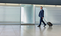 Mature businessman walking with his suitcase in the airport