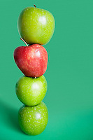 Red and green apples balancing over colored background