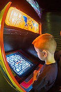 Garden City, New York, USA. December 12, 2015. A six-year-old boy plays the classic 1982 Bally/Midway arcade game Ms. Pac-Man, during Opening Day of Arcade Age exhibit, in an arcade set up at Cradle of Aviation Museum in Long Island. Admission includes unlimited free pay-to-play of video arcade games. Exhibit runs from Dec. 12, 2015 through April 3, 2016.