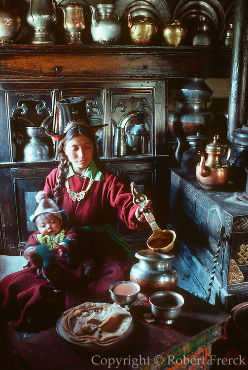 INDIA, LADAKH Ladakhi women and child preparing tea  surrounded by traditional stove and pots  in their kithen in Leh