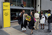 Lady graduates fling their rented mortarboard hats into the air after their graduation eremony, in celebration of their university academic achievement, outside the Festival Hall, on 20th July 2017, on the Southbank, London, England.