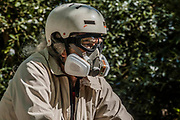 A cyclist opts for a heavy duty gas mask and goggles - Battersea Park is reasonably busy as the sun is out and it is warmer. The 'lockdown' continues for the Coronavirus (Covid 19) outbreak in London.
