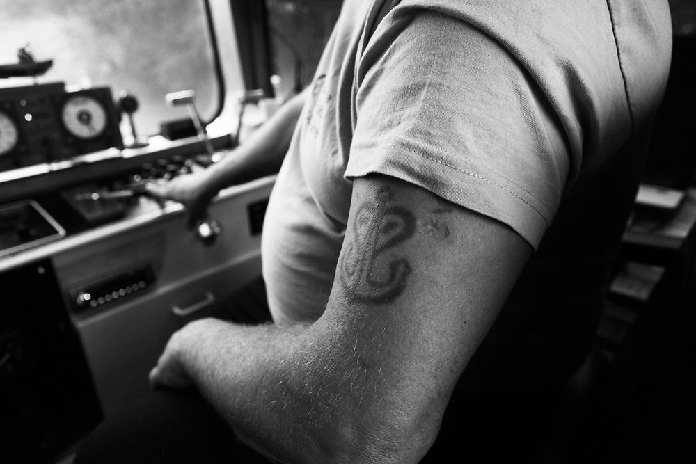 Le bras de Jean-Michel Tirache, conduisant sa péniche baptisée du nom de sa femme, Fabiola.