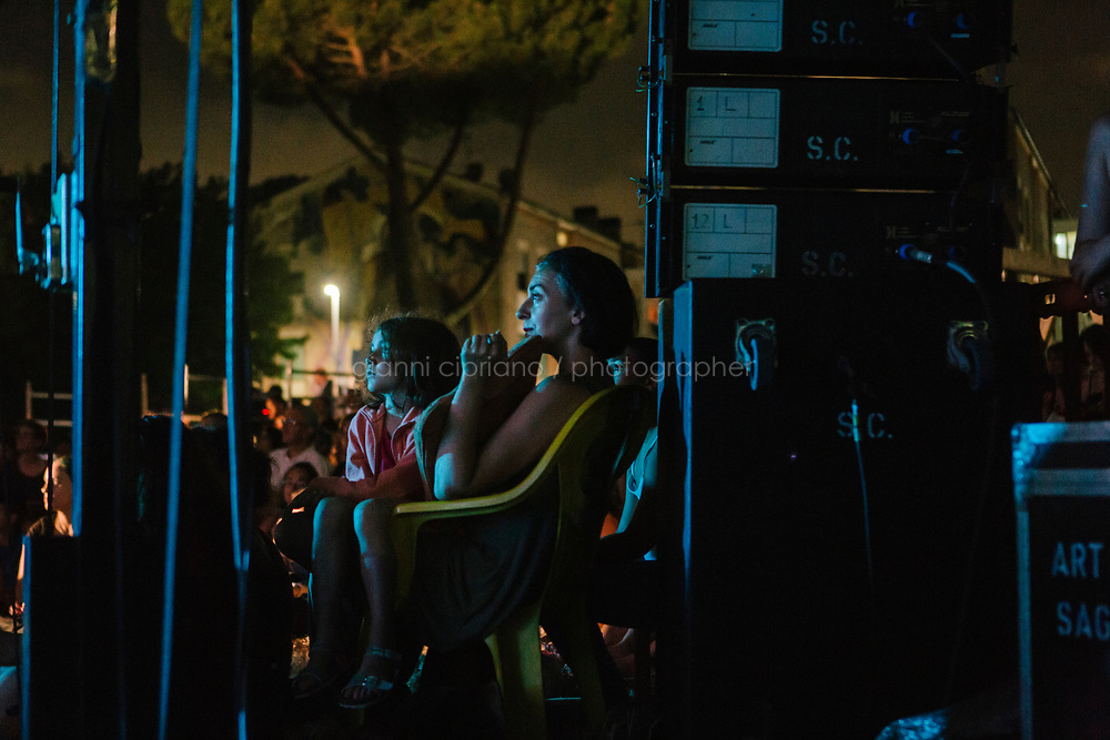 ROME, ITALY - 27 JUNE 2017: The audience watches the premiere of the &quot;Don Giovanni OperaCamion&quot;, an open-air opera performed on a truck in San Basilio, a suburb in Rome, Italy, on June 27th 2017.<br /> <br /> Director Fabio Cherstich&rsquo;s idae of an &ldquo;opera truck&rdquo; was conceived as a way of bringing the musical theatre to a new, mixed, non elitist public, and have it perceived as a moment of cultural sharing, intelligent entertainment and no longer as an inaccessible and costly event. The truck becomes a stage that goes from square to square with its orchestra and its company of singers in Rome. <br /> <br /> &ldquo;Don Giovanni Opera Camion&rdquo;, after &ldquo;Don Giovanni&rdquo; by Wolfgang Amadeus Mozart is a new production by the Teatro dell&rsquo;Opera di Roma, conceived and directed by Fabio Cherstich. Set, videos and costumes by Gianluigi Toccafondo. The Youth Orchestra of the Teatro dell&rsquo;Opera di Roma is conducted by Carlo Donadio.