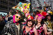 New York, NY - 21 April 2019. A man with an Easter basket hat and two woman in floral hats and dresses at the Easter Bonnet Parade and Festival on New York's Fifth Avenue.