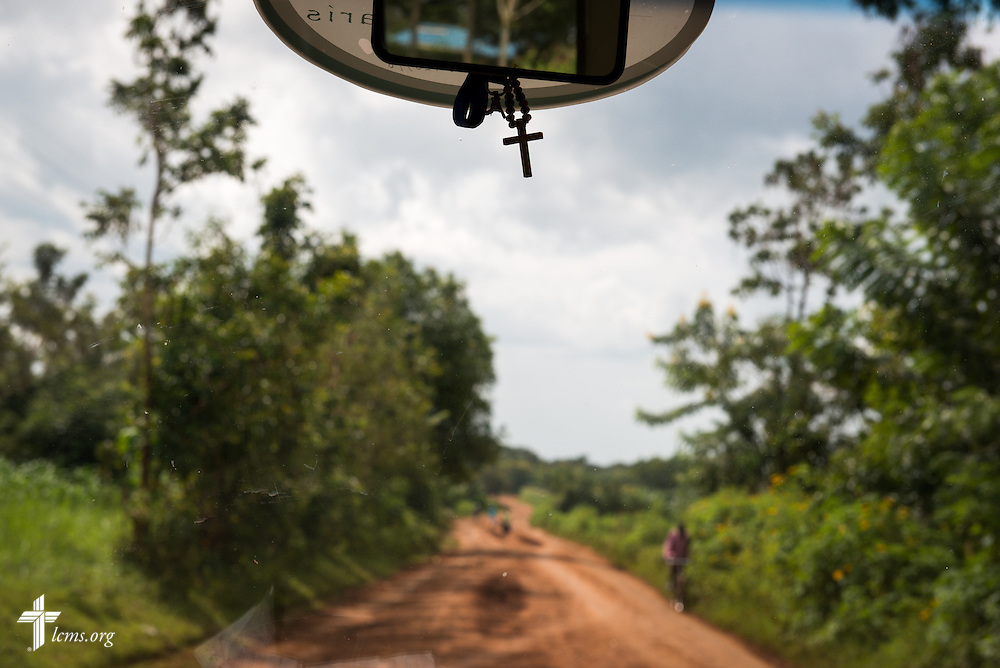 A cross dangles from the rearview mirror in a bus heading to retrieve members of the Mercy Medical Team Thursday, June 12, 2014, in Kakmega County, Kenya. LCMS Communications/Erik M. Lunsford