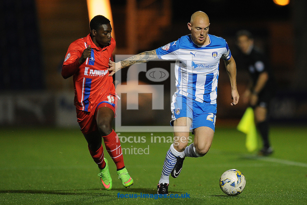Sean Clohessy of Colchester United looks to get past Jermaine McGlashan of Gillingham during the Johnstone's Paint Trophy match between Colchester United and Gillingham at the Weston Homes Community Stadium, Colchester<br /> Picture by Richard Blaxall/Focus Images Ltd +44 7853 364624<br /> 07/10/2014