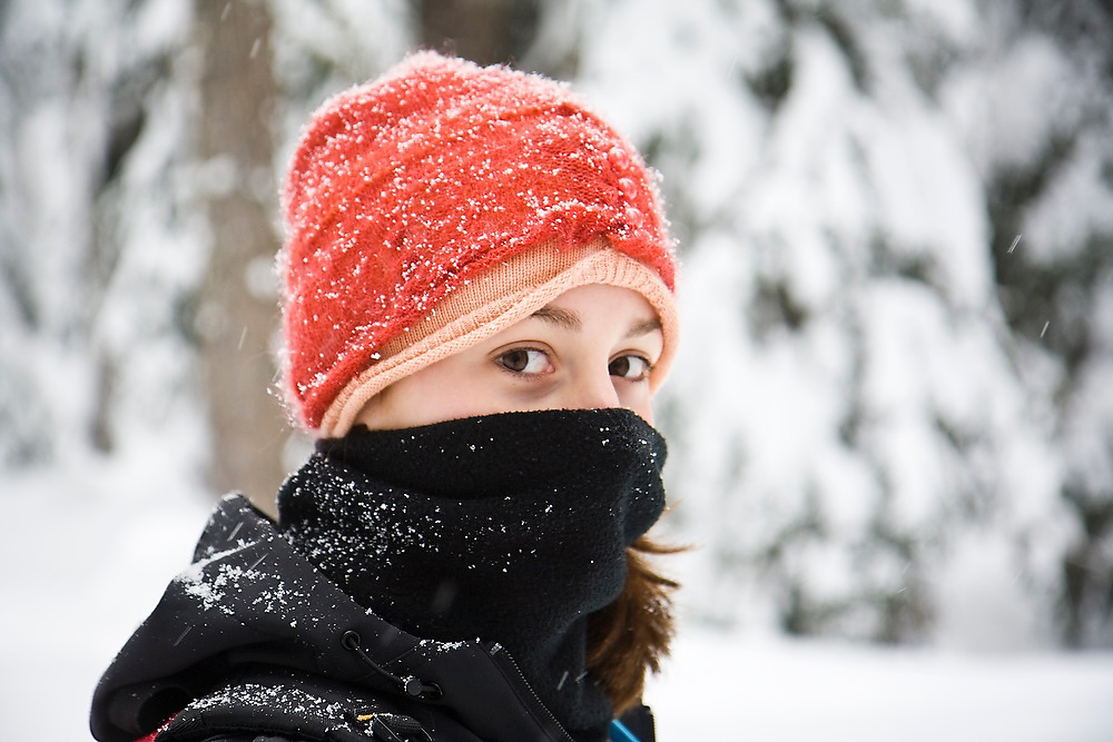 A girl with her face covered hikes through the snow at Commonwealth Basin, near Snoqualmie Pass, Washington.