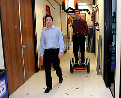 MOUNTAIN VIEW, CALIF., APRIL 8, 2003--GOOGLE--Sergey Brin, Co-Founder & President, Technology  walks and Larry Page, Co-Founder & President, Products (R)  rides a Segway Human Transporter through the halls  at Google's campus headquarters in Mountain View, Calif. They founded the company in 1998.  Photo by Kim Kulish