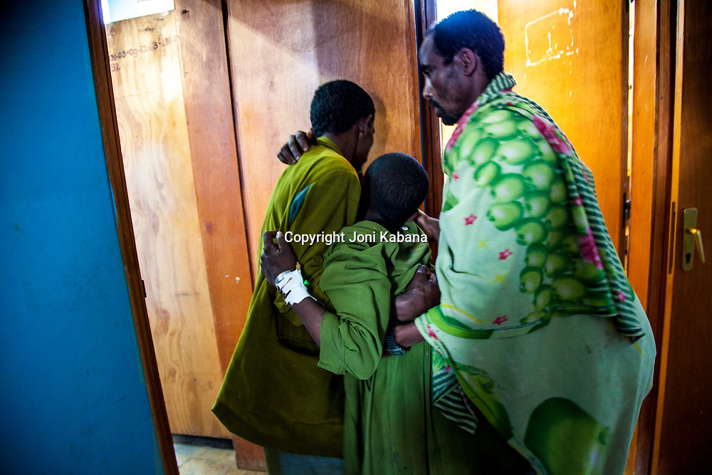 Two brothers carry their sister who is suffering obstructed labor into the operating room at a hospital in rural Ethiopia.
