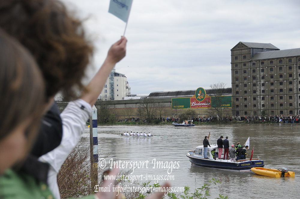 Putney-Mortlake  LONDON. GREAT BRITAIN, 2012 University Boat Race. Raced over the Championship Course. Putney/Mortlake. The White Finish Line Flag, is raised, as CUBC approach the Finish Line, to win the 2012 Baot Race. Saturday 07/04/2012 [Mandatory Credit; Karon Phillips/Intersport-images]..Crews:.CUBC. Bow David NELSON, 2 Moritz SCHRAMM, 3 Jack LINDEMAN, 4 Alex ROSS, 5 Mike THORP 6 Steve DUDEK, 7 Alexander SCHARP, Stroke Niles GARRATT and Cox Ed BOSSON. ..OUBC. Bow Dr. Alexander WOODS 2 William ZENG, 3 Kevin BAUM, 4 Alex DAVIDSON, 5 Karl HUDSPITH, 6 Dr. Hanno WIENHAUSEN, 7 Dan HARVEY, Stroke Roel HAEN and Cox Zoe DE TOLEDO..