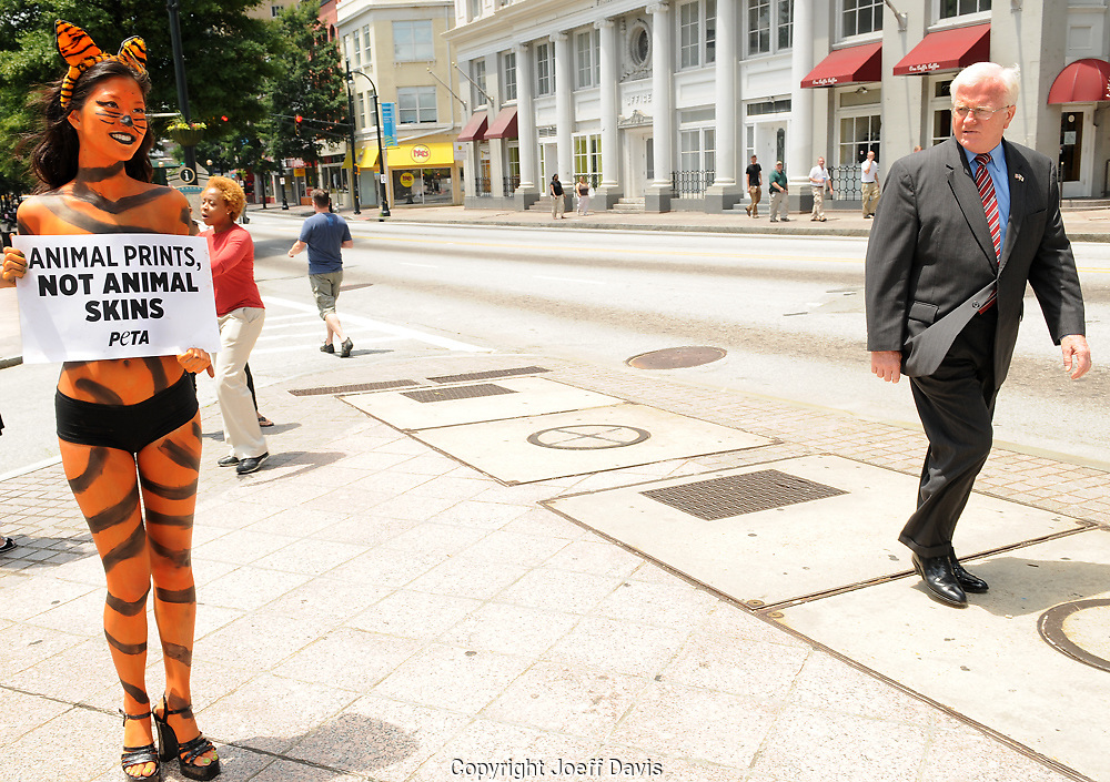 "Animal rights activists -- in town for the city's Fashion Week -- turned heads this afternoon during lunch hour at the corner of Auburn Avenue and Peachtree Street. Dressed up as a lion and tiger in body paint and little else, People for the Ethical Treatment of Animals interns Mayo and Jessica covered their chests with signs that encourage people not to purchase leather, fur and exotic skins. ""We are asking Atlanta's fashion-forward consumers to make a more compassionate choice by choosing animal prints instead of animal skins,"" said Marcia Masulla of PETA. She added that animals on fur farms are ""anally electrocuted, beaten and many times skinned alive."""