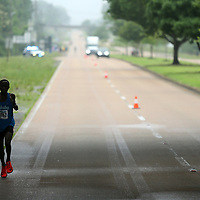 The lead runner runs under the overpass of Gloster Street on McCullough Blvd during the Gumtree Run Saturday morning in Tupelo.