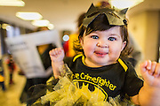 31 OCTOBER 2013 - PHOENIX, AZ:   A child wearing a Halloween costume inspired by Batman is held by her mother in the lobby of the Arizona state capitol during an immigration protest in the capitol Thursday. About 20 supporters of the DREAM Act and the deferred action program of President Barack Obama visited the office of Arizona Governor Jan Brewer to protest her decision to deny drivers licenses to Arizona DREAMERS and immigrants granted deferred action status by immigration authorities. The protest was a part of ongoing series of actions by immigration rights activists in Arizona to protest against anti-immigrant actions taken by Arizona political leaders.   PHOTO BY JACK KURTZ