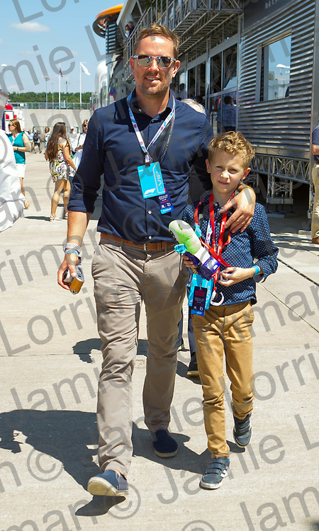 The 2018 Formula 1 F1 Rolex British grand prix, Silverstone, England. Sunday 8th July 2018.<br /> <br /> Pictured: Television presenter Simon Thomas and his son Ethan walk in the paddock ahead of the race at Silverstone.<br /> <br /> Jamie Lorriman<br /> mail@jamielorriman.co.uk<br /> www.jamielorriman.co.uk<br /> 07718 900288