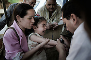 Egypt, Cairo: A mother holds her daughter while she is tattoed in her right wrist with a cross outside Monastery of St.Simon in Manshyet Naser el Moqattam.. ph.Christian Minelli.