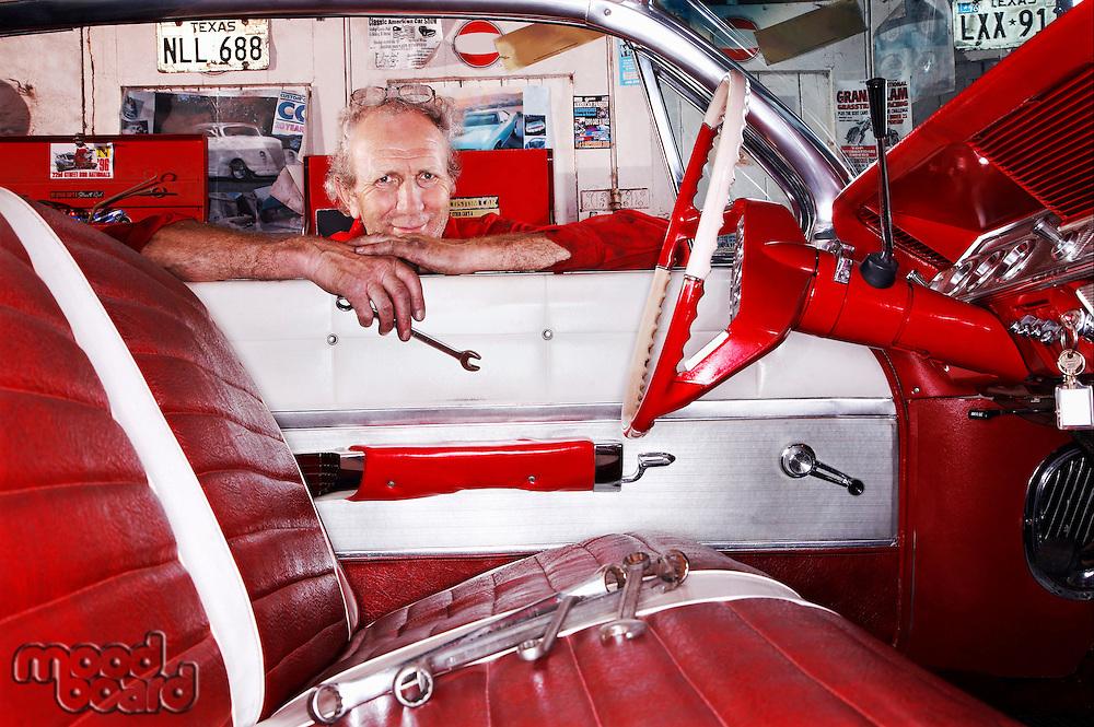 Kent UK portrait of mechanic in garage leaning over car window