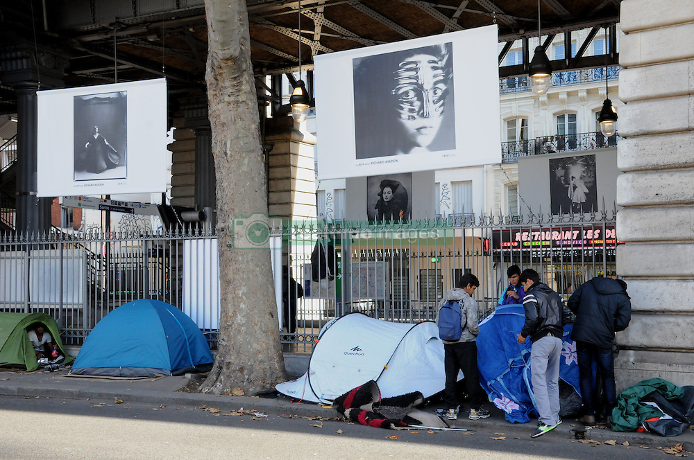 "Migrants stand in street near the Jaures and Stalingrad metro stations, in northern Paris, France, on October 31, 2016, during a police operation aiming at a future evacuation of a migrant camp. An operation of ""administrative control"" was underway on early October 31 in the Jaures/Stalingrad quarter before a future evacuation, whose date has not yet been set, according to a police source. The makeshift camp on the outskirts of the 10th and 19th arrondissements in the north of the capital numbers today 2,500 people, according to the City of Paris. Photo by Alain Apaydin/ABACAPRESS.COM"
