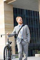 Businessman with bicycle looking away while standing outdoors