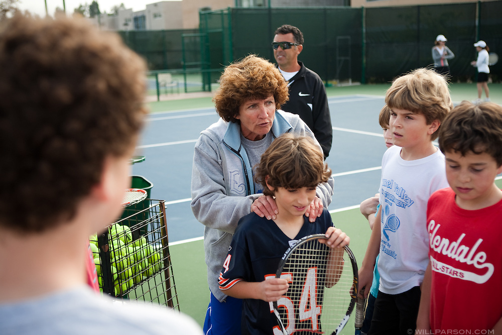 Angela Horacek squeezes the shoulders of Ian Mottale, 10, while talking to tennis camp participants.