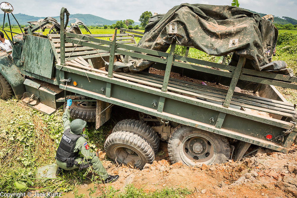 08 JULY 2013 - MAYO, PATTANI, THAILAND: A member of a Thai army bomb squad inspects an Army truck destroyed by an IED in Pattani Monday. Eight Thai soldiers were injured - one seriouly and seven with minor injuries - when their truck was hit by an IED outside Mayo, Pattani province in southern Thailand Monday. The soldiers were returning from a teacher protection mission when their truck ran over the explosive. The attack was thought to be conducted by Muslim insurgents who have been battling the Thai government for greater autonomy. The conflict in southern Thailand has claimed about 5,000 lives since 2004.    PHOTO BY JACK KURTZ