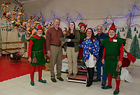 Scott Myers standing in for Mayor Ed Engler receives the key to Christmas Village from this years Mayor Emily Theberge at opening night Thursday evening.  (l-r) Twinkle, Scott Myers, Emily Theberge, Egg Nog, Patty Derosier, Bob Hamel and Tinsel.  (Karen Bobotas/for the Laconia Daily Sun)