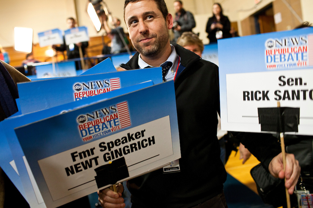 A debate staff member holds signs in the spin room following the WMUR/ABC News Debate at Saint Anselm College on Saturday, January 7, 2012 in Manchester, NH. Brendan Hoffman for the New York Times