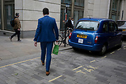 A tall man wearing a blue suit strides past a parked taxi in the same blue, in the City of London - the capital's financial district, on 4th June 2018, in London, England.