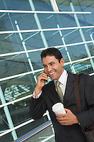 Businessman using mobile phone with take away coffee outside office building