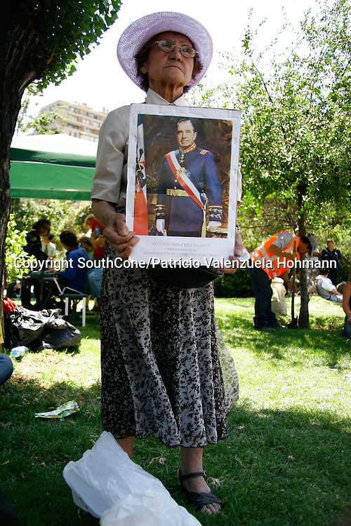 An elder holds a Pinochet portrait.<br /> December 2006, The Chilean Dictator Augusto Pinochet died in Santiago Chile. As news spread thousands went out the streets either to celebrate o mourn Pinochet who lead the 1973 coup that overthrew the democratically elected president Salvador Allende. Pinochet's 17 year regime killed and disappeared around 4.000 people, tortured and exile around 20.000. On 1989 he lost elections and democracy was regained. He died on late December 2006. December 2006, The Chilean Dictator Augusto Pinochet died in Santiago Chile. As news spread thousands went out the streets either to celebrate o mourn Pinochet who lead the 1973 coup that overthrew the democratically elected president Salvador Allende. Pinochet's 17 year December 2006, The Chilean Dictator Augusto Pinochet died in Santiago Chile. As news spread thousands went out the streets either to celebrate o mourn Pinochet who lead the 1973 coup that overthrew the democratically elected president Salvador Allende. Pinochet's 17 year.